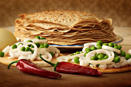 pancakes on a plate and pancakes with rice and green peas, red pepper lie on a wooden board