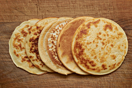 four round pancakes on a wooden table