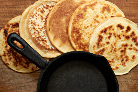 four round pancakes and cast iron skillet on a wooden table Stock Photo