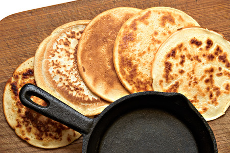 Four different round pancake and a small cast iron skillet lie on a wooden board