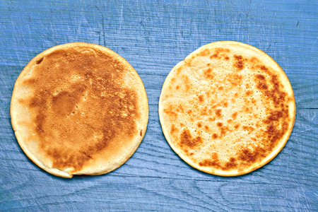 two yellow pancakes on a old wooden board