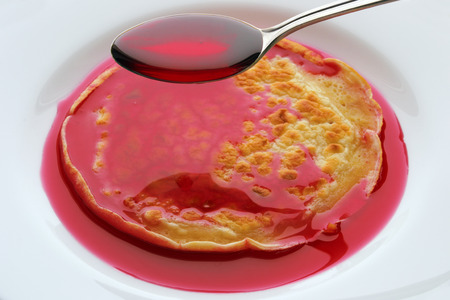 spoon with cherry syrup over pancakes on a white plate