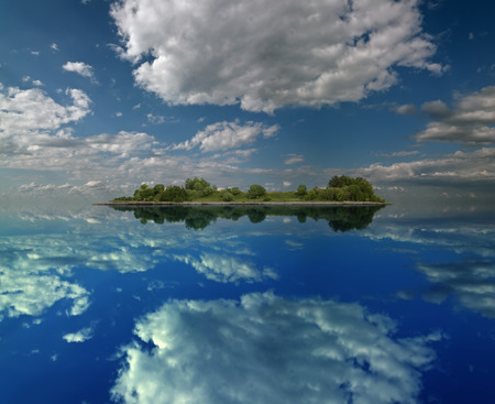 island covered with green trees and clouds reflected in calm water Stock Photo