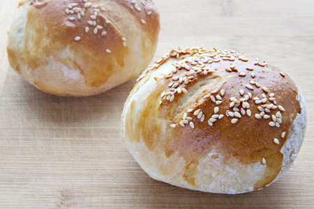 two buns with sesame seed on a wooden board