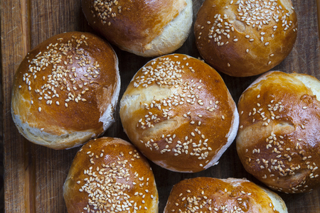 buns with sesame seed on a wooden board