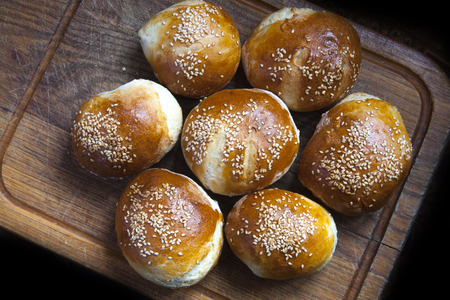 pastries buns, sprinkled with sesame seeds on a wooden board