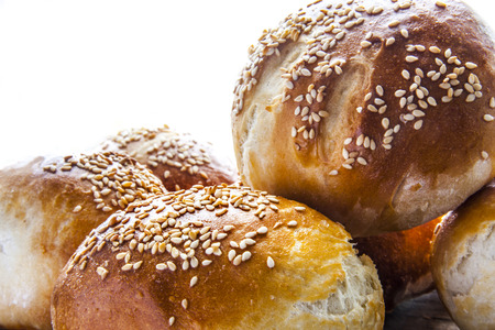 buns with sesame seed on a wooden board. whtie background