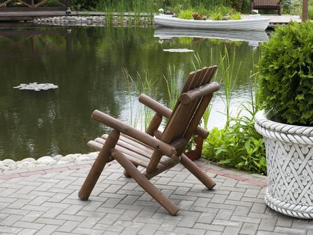 silla de madera: Silla de madera en la orilla de la laguna. Parque. Foto de archivo
