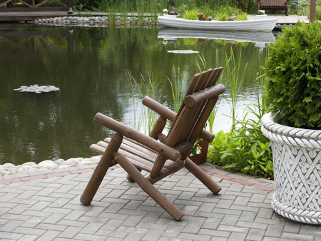 wooden chair: Wooden chair on the shore of the pond. Park.
