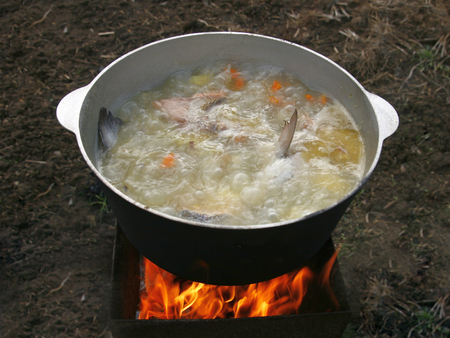fish fire: Cooking fish soup in a cauldron over the fire. Stock Photo