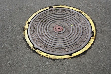 manhole cover: manhole cover with yellow edging Stock Photo