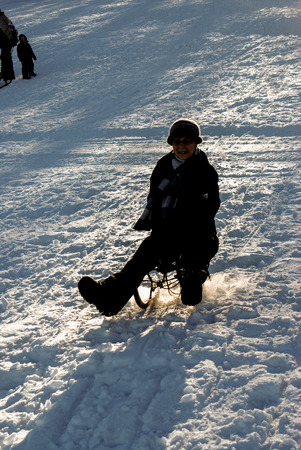 sledging people: a person is sledding downhill on white snow, backligt