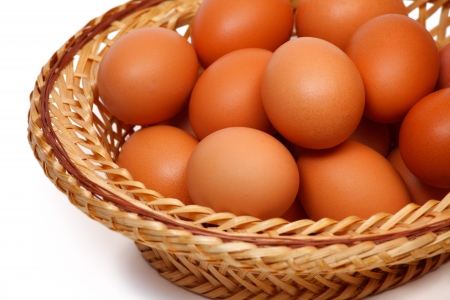 boiled eggs: Colored eggs in straw plate Stock Photo