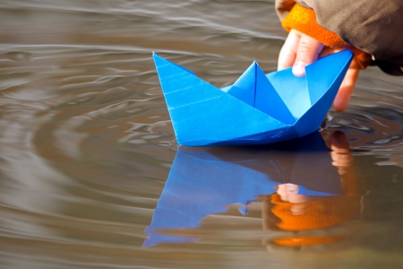 yellow boats: Childs hand and blue paper boat in water in spring Stock Photo