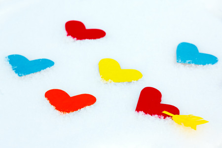 Many paper colored heart shapes in snow photo
