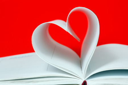 Heart shape of diary pages on a red background photo