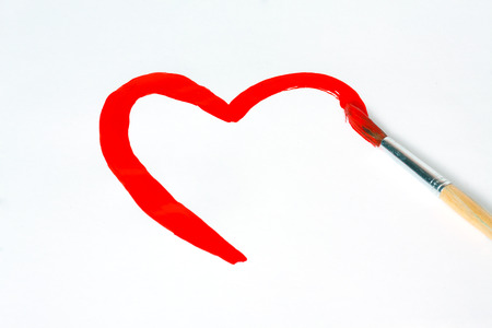 Heart shape drawn brush with red paint photo