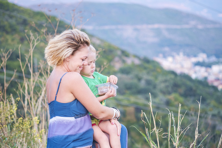 Close-up portrait of a young beautiful mother with her little son is resting in nature. A woman holds a child in her arms. Mountain covered with forest is seen in the background. Happy family and mother love and care concept