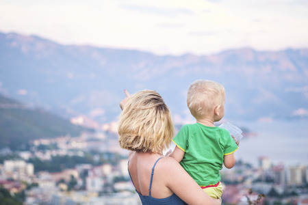 Close-up portrait of a young beautiful mother with her little son is resting in nature. Mother holds her son in arms and tenderly kisses him. In the background we can see a town, mountain and sea. Happy family and mother love and care concept