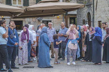 Kotor, Montenegro, August 28, 2018: group of Muslim tourists from Asia in national dress on an excursion in Kotor inspects local attractions. Young woman takes pictures of an ancient building on a smartphone