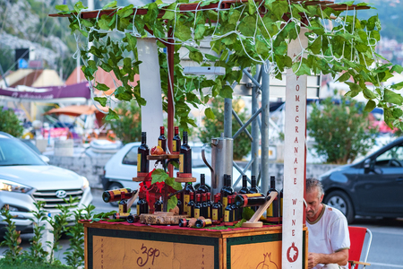 Kotor, Montenegro, August 28, 2018: An elderly man sells on the street from the counter Montenegrin national wine Vranac and others. Road with cars on the background 報道画像