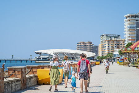 Durres, Albania, August 21, 2018: Embankment of the Albanian city Durres. Citizens and tourists walk along the sea. In the foreground is a group of tourists with a child. In the background are residential buildings Редакционное