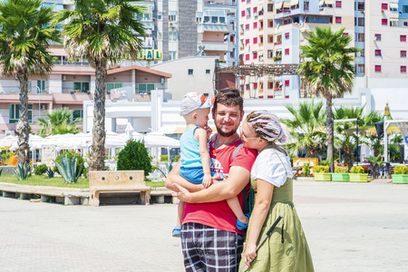Durres, Albania, August 21, 2018: Family of tourists is walking along the promenade. The father holds the little son in his arms. A young woman with multi-colored dreadlocks lay her head on her husbands shoulder and smiles at the child