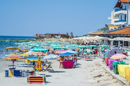 Durres, Albania, August 21, 2018: The main city beach of the Albanian city Durres near the waterfront. We see a calm azure sea, a sandy beach, many colorful umbrellas and beach chaise longue, a crowd of tourists and locals