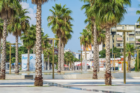 Durres, Albania, August 21, 2018: The promenade of the Albanian city Durres, planted with tall palm trees. There is a fountain in the center of the frame, and residential buildings are visible in the background Editorial