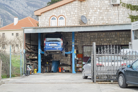 Bar, Montenegro, February 04, 2019: View of a small local car repair shop. A car is on the lift for diagnostics and repair
