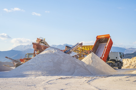 Kotor, Montenegro, February 15, 2019: The territory of a сement plant for the production of building materials. In the open area a large truck brought sand and pours it into a heap