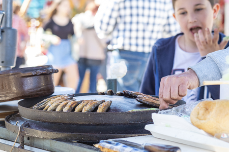 Virpazar, Montenegro, March, 24, 2019: Festival of wine and fish in the Montenegrin town Virpazar. Montenegrins fry and sell fish on the street for festival guests Editorial