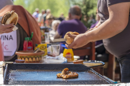 Virpazar, Montenegro, March, 24, 2019: A fat young guy makes hamburgers with fried beef succulent appetizing cutlets and sells them to the guests of the festival