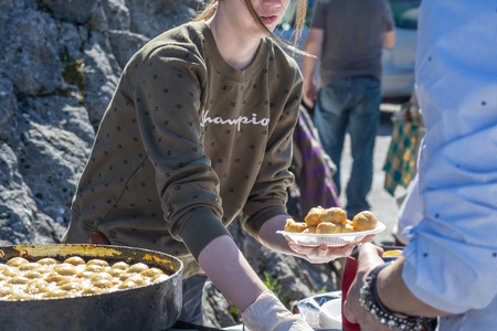Virpazar, Montenegro, March, 24, 2019: National festival of wine and fish in the Montenegrin town Virpazar. Young girl roasts dumplings with cheese on a large iron pan - a local Montenegrin dish - and sells them to the guests of the festival Editorial
