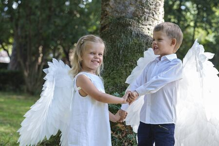 Two little blond children, brother and sister, dressed as angels with white wings, walk in the park. Trees crowns and green tree branches are visible in the background