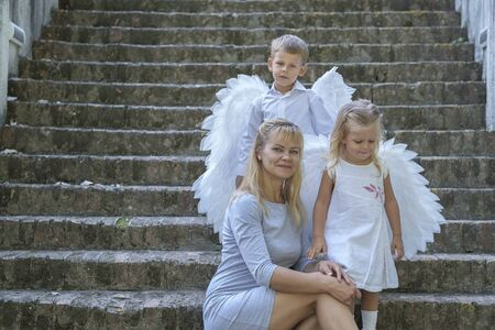 Young blonde woman with two little children – a boy and a girl – sits on the stone steps of an ancient building. The children are dressed as angels with white wings