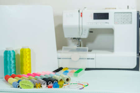 Seamstress's work table - close-up of multi-colored thread coils and other sewing accessories, white electric sewing machine in the background in blur