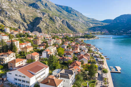 Aerial photo of the coastline of the Adriatic sea bay, small Montenegrin town. Water in the sea is turquoise, pure and clear. White boats swaying on the waves and yachts sailing on the sea Standard-Bild