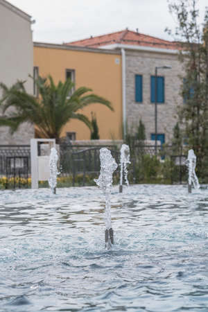 Fountains on the background of a stone residential building in the traditional Balkan style on the street of the seaside town. Palm trees grow near the building