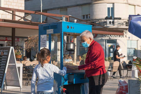 Tivat, Montenegro, October, 20, 2020: Walk along the promenade of the seaside town. A little girl is buying popcorn from a popcorn seller. The seller is an elderly woman in a protective medical mask