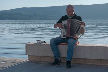 Tivat, Montenegro, October, 20, 2020: Elderly gray haired man is sitting on the embankment on the parapet against the sea and is playing the accordion collecting money from passers-by Editorial