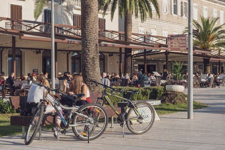 View of the busy waterfront of a seaside town. Two young girls are talking, sitting on a bench, their bicycles are standing next to them, in the background a view of an open cafe filled with people