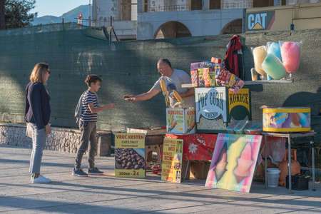 Tivat, Montenegro, October, 20, 2020: Boy and his mother walk along the embankment in autumn, on a warm Sunny day. A boy buys popcorn from an old man - street salesman selling popcorn and colorful cot