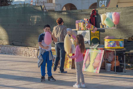 Woman with two children (boy and girl) walk along the embankment. She buys them a cotton candy from a street salesman. Children are eating colorful cotton candy with appetite Editorial