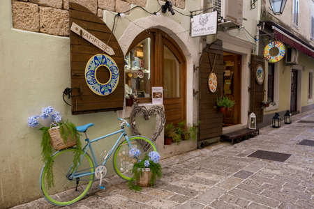 Street of the Old Town, paved with stone. At the entrance to the gift shop, there is a decorative bicycle with two baskets of flowers for decoration. Store has wooden shutters on the windows Editorial