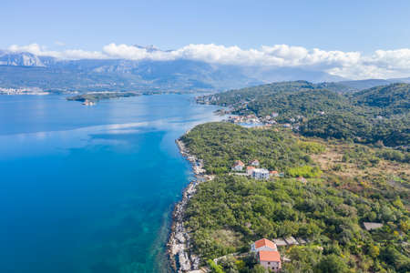 Aerial photo of the coastline of the Adriatic sea bay, small Montenegrin town in autumn. Sunny day, blue sky, mountains are visible in the distance. Water in the sea is turquoise, pure and clear