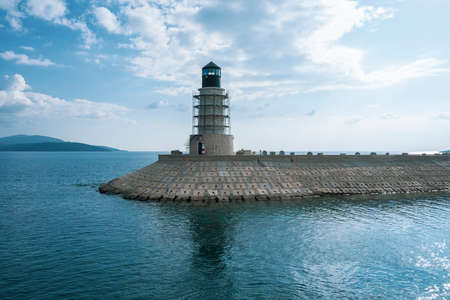View of the lighthouse from the shore on a sunny day. The lighthouse stands on a concrete pontoon. The sea is turquoise, the sky is blue