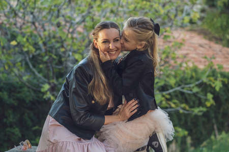Mom and daughter take a walk in the park in autumn, both wearing pink dresses and black leather jackets, blondes with long hair. Little daughter hugs mom and whispers something in her ear