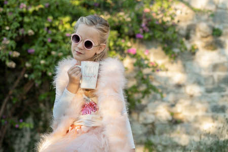 Seven-year-old girl, blonde with long hair, wearing round sunglasses and a pink fur vest, on a walk in the park is sitting on a bench with a cup of tea in her hand