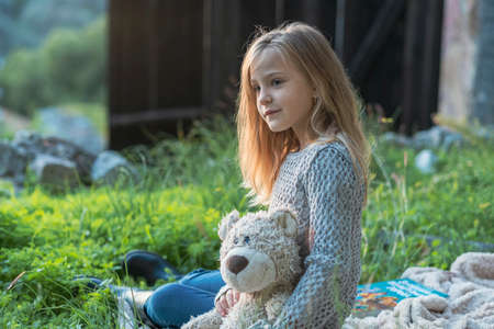 Little girl with long blond hair in a knitted sweater on a picnic in the fall in the park is sitting on a blanket spread on the grass and holding a teddy bear